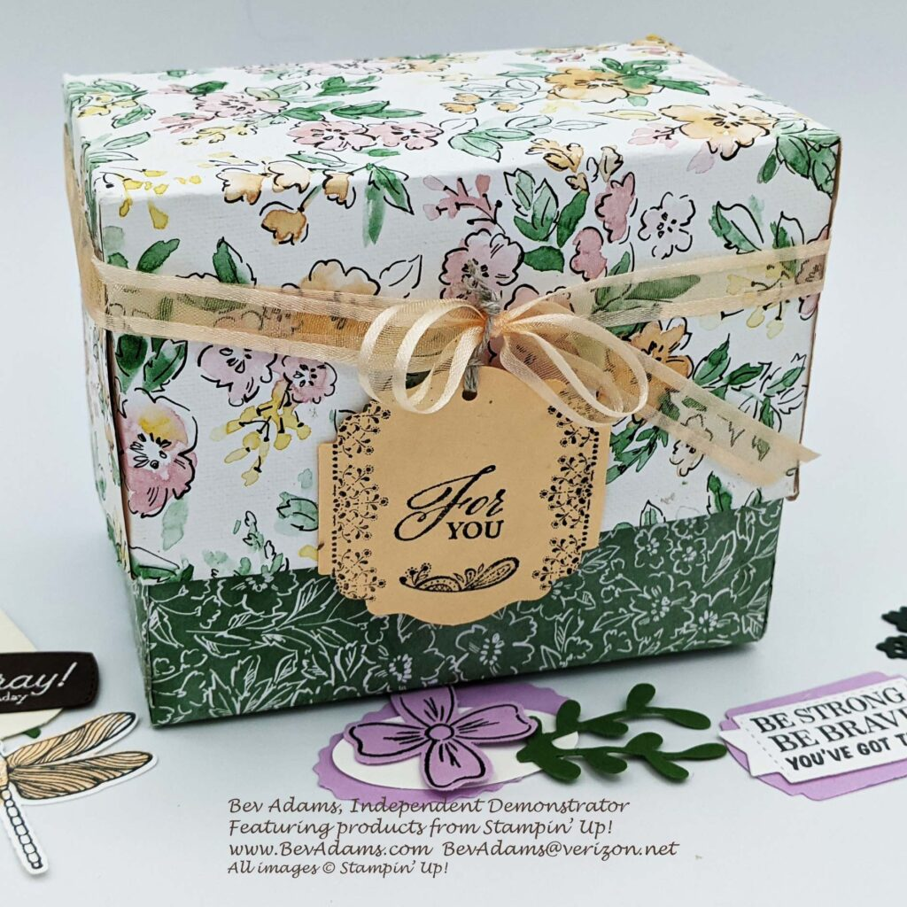 A hand-made box, decorated with a ribbon and a tag. It's made for filing tags as a resource for future projects.